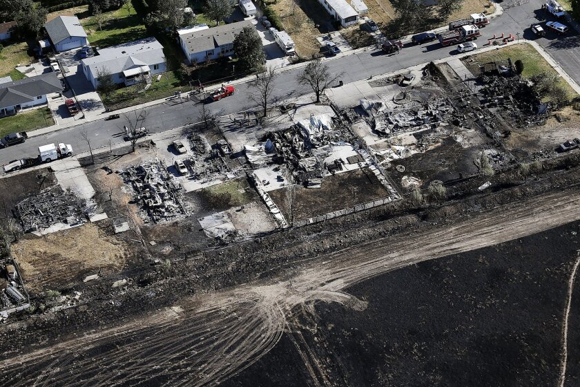 This aerial photo shows the charred remains of homes following a fire in Tooele, Utah on Wednesday, July 20, 2016. Firefighters contained a blaze fueled by wind that ripped through a Utah trailer park, displacing dozens of people and destroying multiple homes. (Ravell Call/The Deseret News via AP)