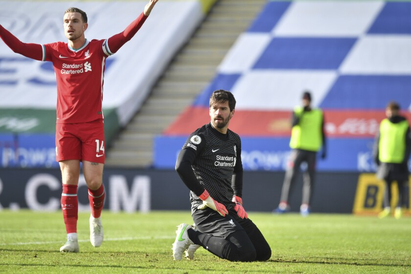 Liverpool's Jordan Henderson, left, and Liverpool's goalkeeper Alisson react to the linesman after Leicester's James Maddison scores his side's opening goal during the English Premier League soccer match between Leicester City and Liverpool at the King Power Stadium in Leicester, England, Saturday, Feb. 13, 2021. (Paul Ellis/Pool Photo via AP)