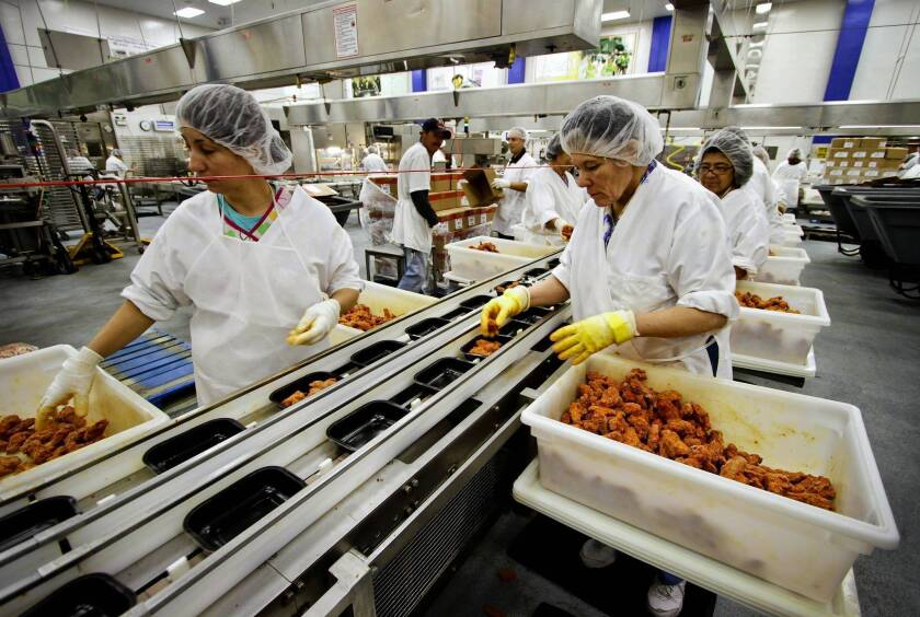Workers in an L.A. Unified kitchen pack student meals in 2011. The district has joined five other major urban school districts in a push to make wholesome food and eco-friendly practices a national standard.