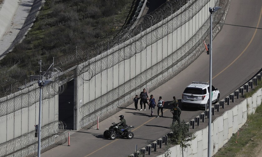 FILE - In this Dec. 16, 2018, file photo, Honduran asylum seekers are taken into custody by U.S. Border Patrol agents after the group crossed the U.S. border wall into San Diego, in California, seen from Tijuana, Mexico. The state of California is freeing up to $28 million to help asylum-seekers released in the U.S. with notices to appear in court with hotels, medical screenings, and transportation. California's generosity is a stark contrast to Arizona and Texas, where border state officials have challenged and sharply criticized President Joe Biden's immigration policies. (AP Photo/Moises Castillo, File)