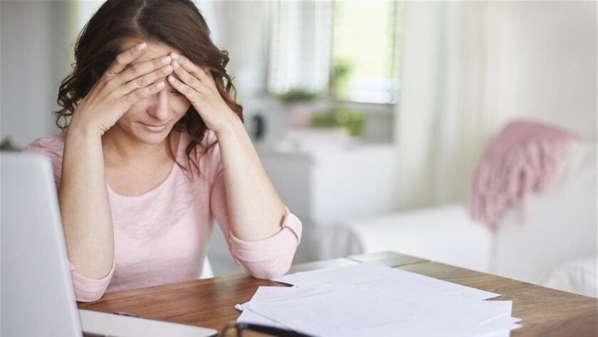 A woman with signs of stress and depression sits at a desk
