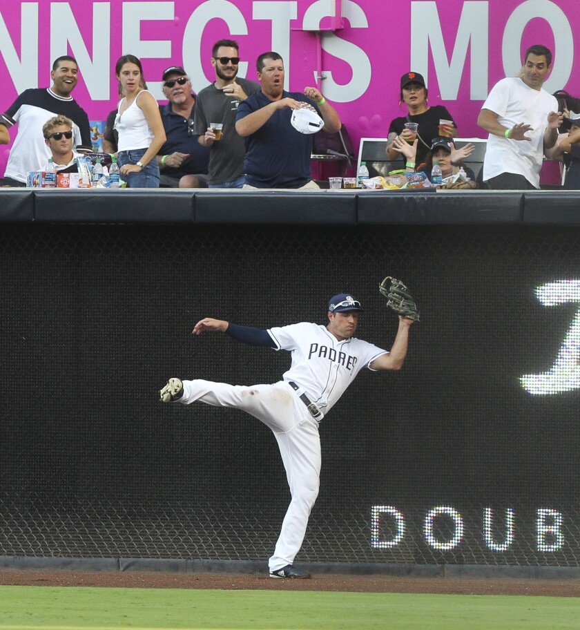 The Padres' Hunter Renfroe hits the wall after catching a hit by the Giants' Joe Panik in the fifth inning against the Giants at Petco Park on Saturday, July 27, 2019 in San Diego, California.
