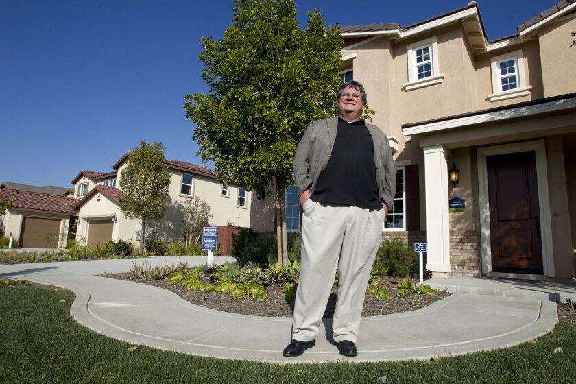 Executive Director of RESNET Steve Baden stands in front of model homes for a Meritage Homes housing development in Oceanside on Monday.