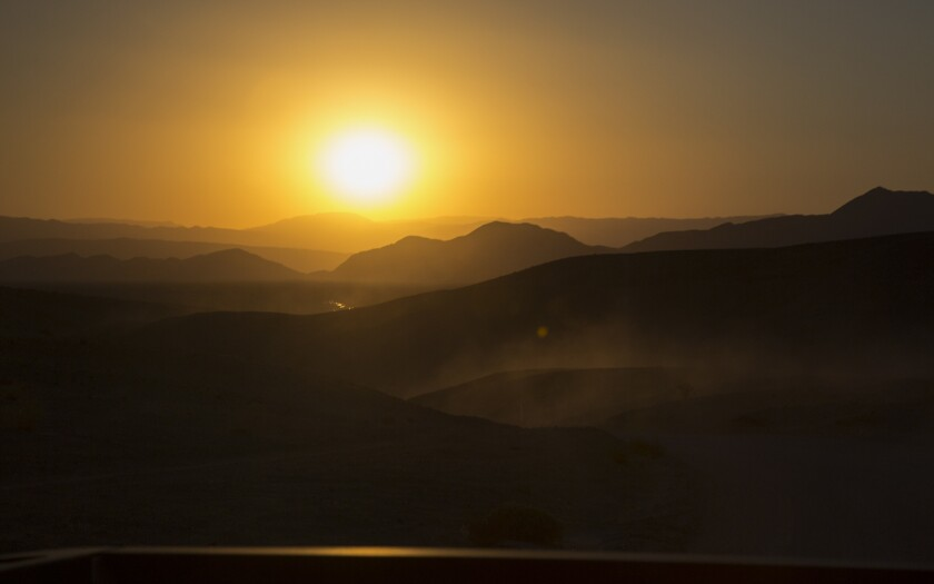 The sun sets over the mountain ridges and the Amargosa River in the Mojave Desert, near the Dumont Dunes in Silurian Valley.