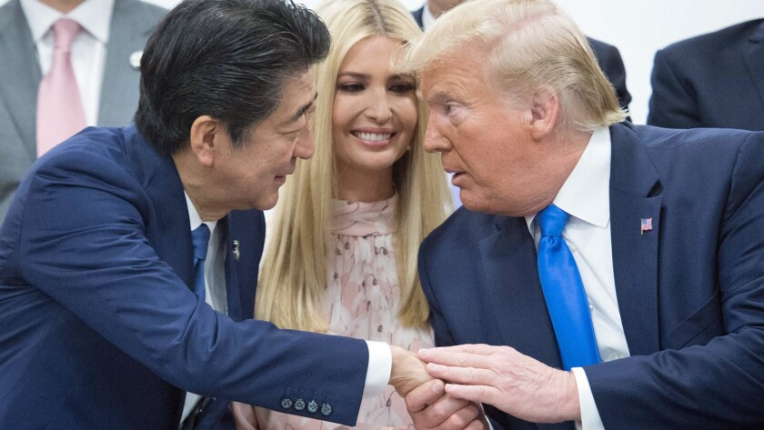 President Trump shakes hands with Japanese Prime Minister Shinzo Abe as Ivanka Trump looks on in Osaka.