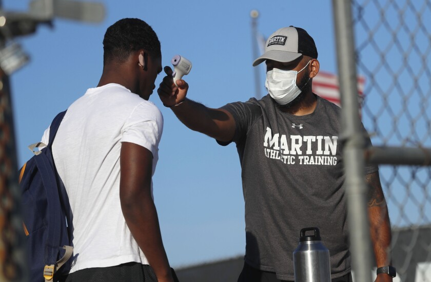 Before entering the field gates for football strength and conditioning camp at Arlington Martin High School, athletic Trainer Joey Pena, right, uses a thermometer on the forehead of sophomore running back Gervawn Neville for a temperature check Thursday, June 18, 2020, in Arlington, Texas. While states have been easing the economic and social lockdowns prompted by the coronavirus pandemic, some are now letting high school athletes return for summer workouts before teachers have even figured out how they are going to hold classroom instruction. (AP Photo/LM Otero)