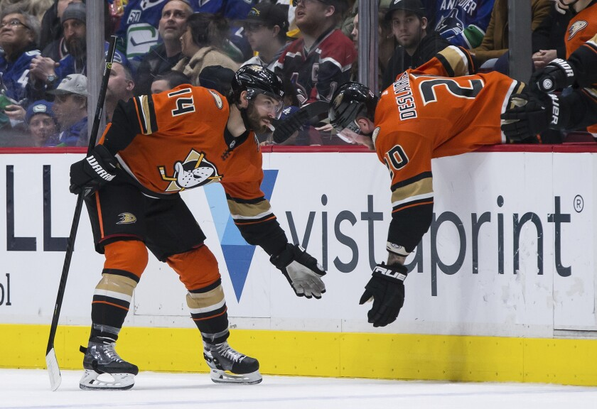 Ducks forward Adam Henrique, left, celebrates with teammate Nicolas Deslauriers after scoring during the second period of the Ducks' 5-1 win Sunday.