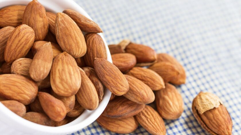 Roasted almonds, salt in bowl of white on the tablecloth. Almonds are rich in nutrients, vitamins, and minerals that are essential to the body.