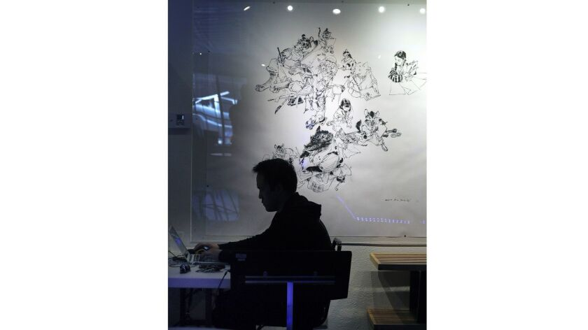 Media relations manager John Park works on a project in front of artwork that seems to flow from his