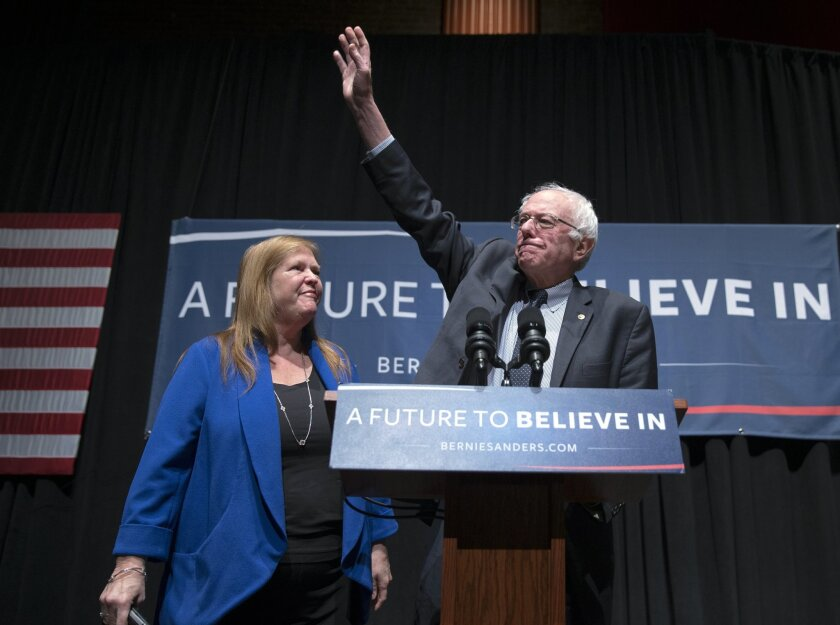 In this Feb. 16, 2016, photo, Jane Sanders watches as her husband Democratic presidential candidate, Sen. Bernie Sanders, I-Vt. waves during a town hall meeting at Burke High School in Charleston, S.C. (AP Photo/Evan Vucci)