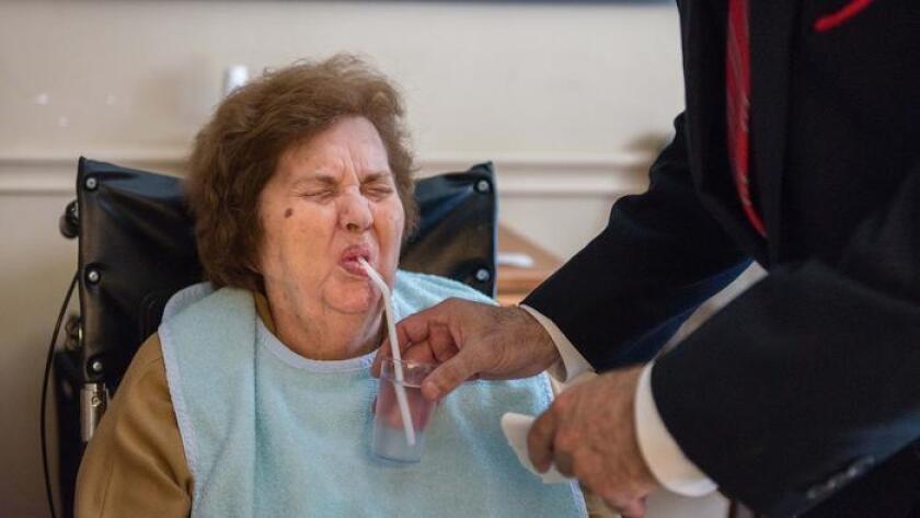 James Morris le da el almuerzo a su madre, Georgina Morris. Según él, la mujer se contagió de una virulenta cepa de la bacteria Clostridium difficile poco después de ingresar a un asilo de ancianos en Sylmar, en 2015 (Heidi de Marco / Kaiser Health News).