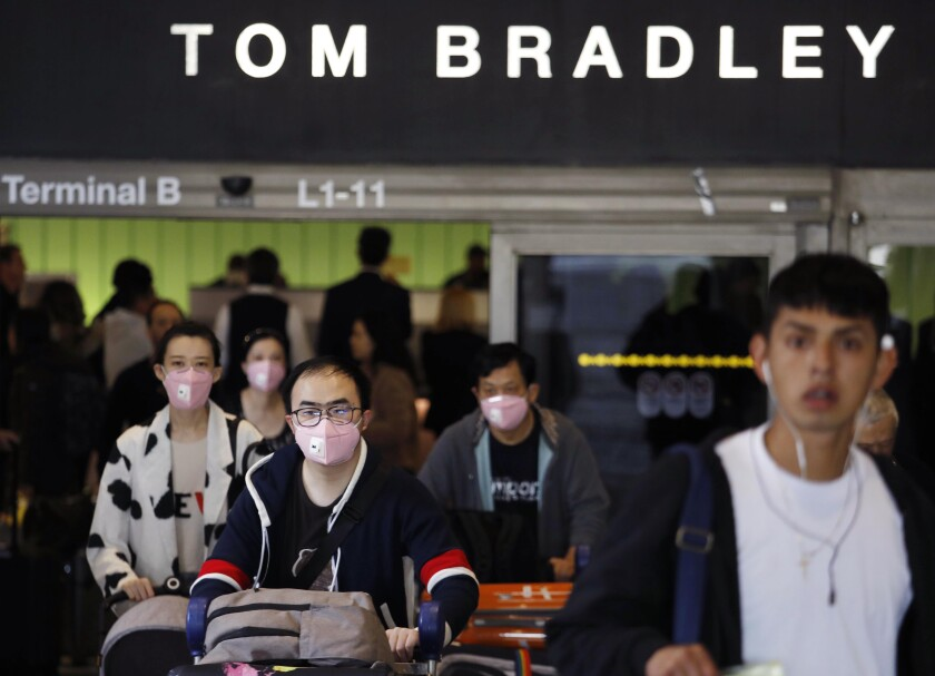 """""""Airlines are trying to be accommodating,"""" one travel industry analyst says, """"but they're giving out refunds only on a case-by-case basis"""" in response to the coronavirus. Above, travelers arriving at Los Angeles International Airport."""