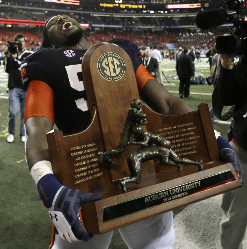 Auburn offensive linesman Avery Young (56) carries the championship trophy after the second half of the Southeastern Conference NCAA football championship game against Missouri, Saturday, Dec. 7, 2013, in Atlanta. Auburn won 59-42. (AP Photo/David Goldman)