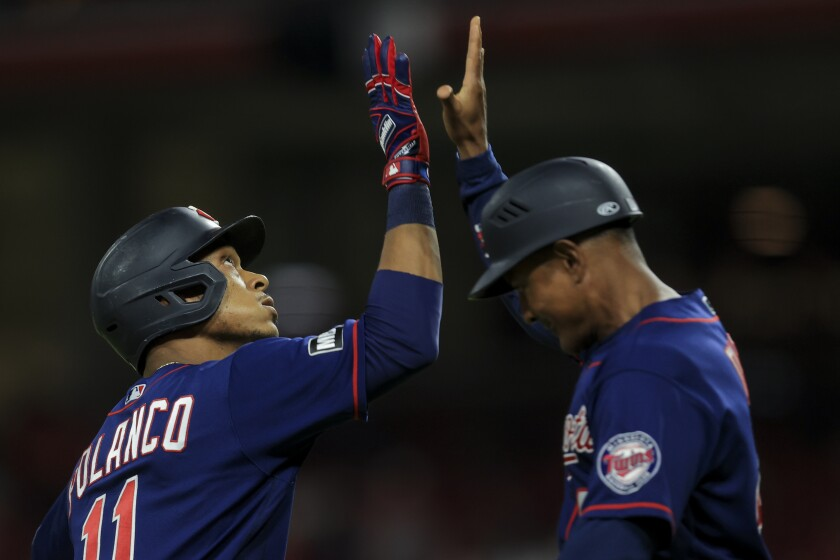 Minnesota Twins' Jorge Polanco, left, high-fives Tony Diaz, right, after hitting a three-run home run during the ninth inning of a baseball game against the Cincinnati Reds in Cincinnati, Tuesday, Aug. 3, 2021. (AP Photo/Aaron Doster)