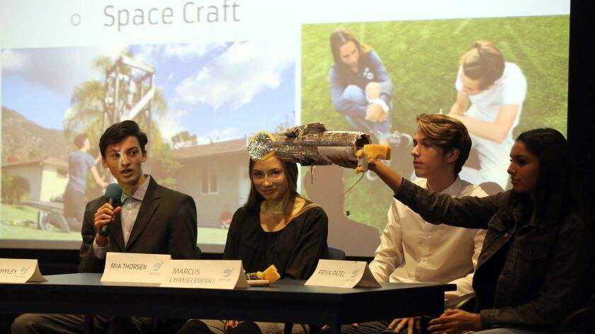 Caleb Whyley, 17, left, from Space Craft company answers questions about his companies space craft