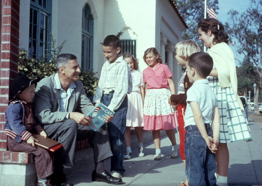 """Author Dr. Seuss holds a copy of """"The Cat in the Hat"""" and is surrounded by kids."""