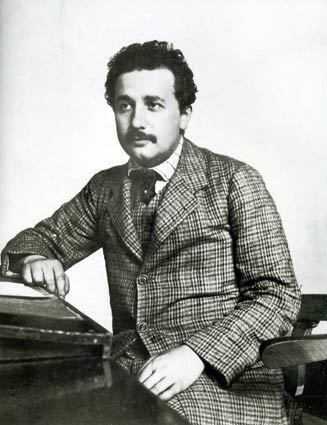 """""""Albert Einstein: The Persistent Illusion of Transience"""" reveals an enlightening collection of documents and photos that bring the Nobelist to life. Shown in his mid-20s in this circa-1905 photo, Einstein sports a tailor-made plaid suit while seated at his Bern, Switzerland, patent office post."""