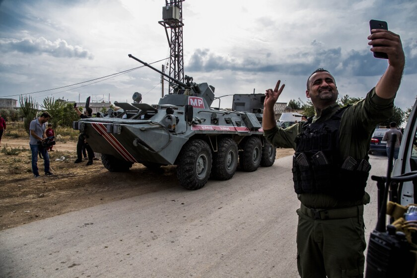 A member of the Kurdish Asayish, or the Internal Security Forces, takes a selfie by an Russian military vehicle during a patrol near the Syrian-Turkish border.