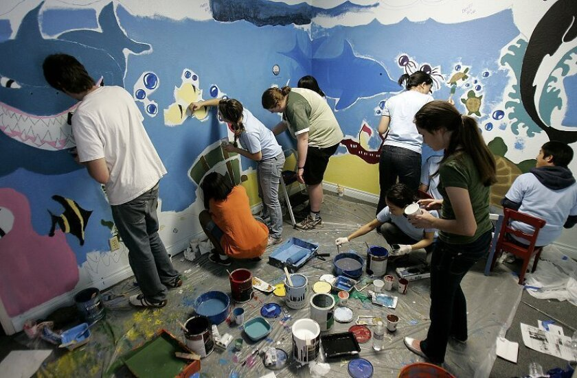 Recruits from Volunteer San Diego, including students with the Justice Corps and Students Actively Volunteering for You, painted a children's mural in Hannah's House on Monday.