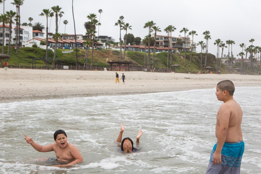 From left, Bryan Lucero, 10, Jocelyn Corado, 8, and Nery Gonzales, 11, play in the surf near the San Clemente Pier.
