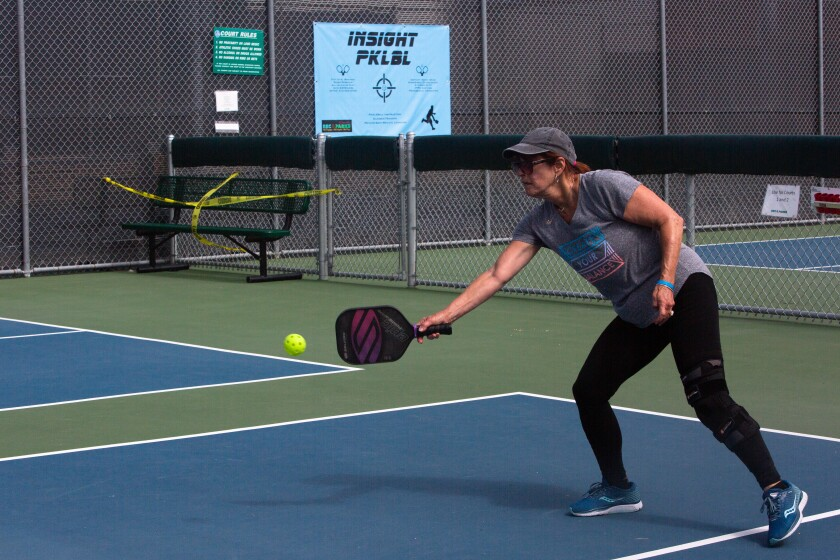 A woman plays pickleball