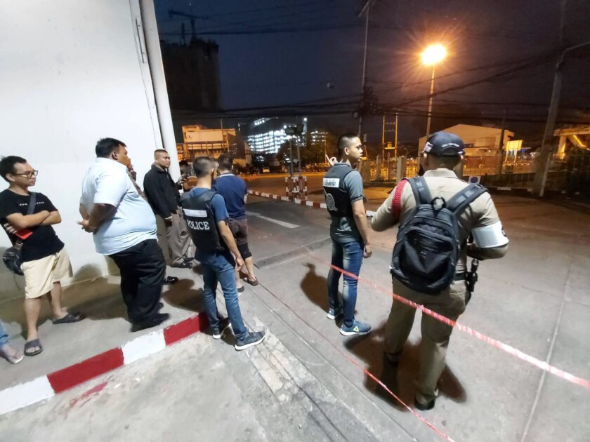 Police and bystanders near the scene of a mass shooting Saturday at the Terminal 21 mall in Nakhon Ratchasima, Thailand.