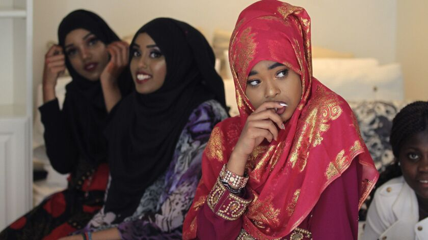 Ayan Yusuf, 16, of Somalia, foreground, with Zuhur Ahmed, 15, center, and her sister Sumya Ahmed, 17, both from Kenya, are dressed in native costume waiting to walk the runway at a fashion show Sunday in Leucadia featuring young women who are recent refugees to the U.S.