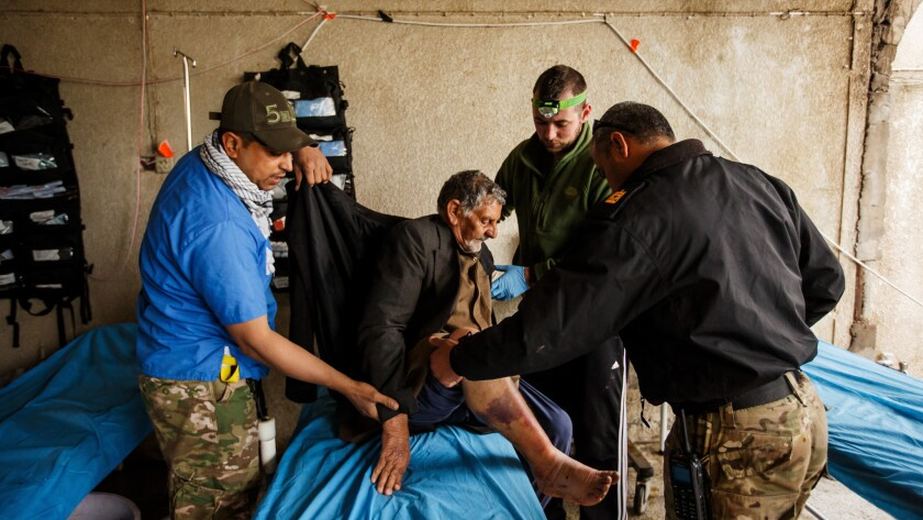 Tom Ordway, 32, second from right, a firefighter from Lake George N.Y., and Maj. Tarek Gazali, right, treat Jadwaa Hamad, 72, at a field clinic near the front lines in Mosul, Iraq. Hamad is suffering from a severely infected burn wound from a recent airstrike.