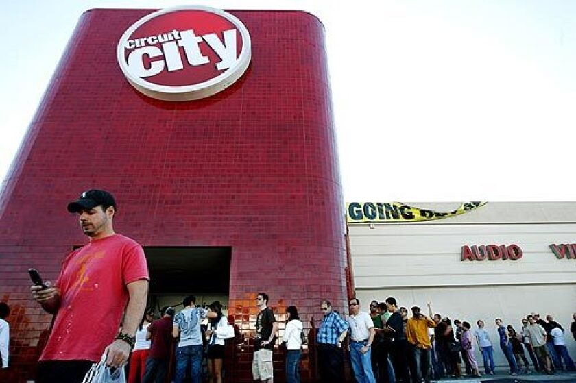 Shoppers wait in line to purchase discounted items at a Circuit City in Los Angeles. The bankrupt Virginia-based electronics retailer is shutting down its 567 U.S. stores and laying off 34,000 workers. More photos >>>