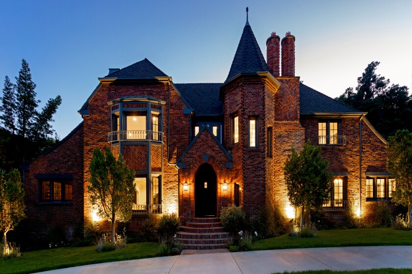 """Called the Palmateer House for its original owner, the English Tudor Revival-style home was designed by L. Milton Wolf, the architect and Hollywoodland developer known for the landmark """"Wolf's Lair"""" on Durand Drive. A two-year restoration has brought the handsome brick residence into the new century while staying true to its original details. Listed for $8.195 million, the two-story home recalls the roaring '20s with its grand formal rooms, period fixtures and original details. A subdued study and speakeasy-inspired wet bar draw the eyes from the living room. Outside, grounds of about half an acre hold a bluestone swimming pool, a pavilion with a kitchen/bar and a matching guest cottage."""