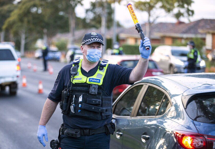A police officer directs traffic at a roadblock in suburban Melbourne, Australia, Thursday, July 2, 2020. Thousands of residents in dozens of suburbs of Melbourne, are preparing to lockdown for a month with the Victoria state premier warning a state-wide shutdown is possible if coronavirus cases continue to rise. (Daniel Pockett/AAP Image via AP)
