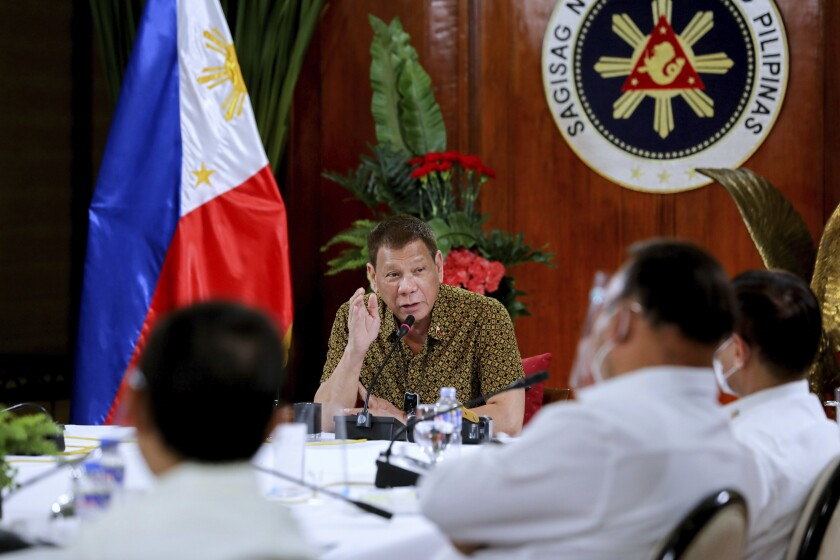 In this photo provided by the Malacanang Presidential Photographers Division, Philippine President Rodrigo Duterte, center, gestures as he meets members of the Inter-Agency Task Force on the Emerging Infectious Diseases at the Malacanang presidential palace in Manila, Philippines late Monday Sept. 28, 2020. Only one southern Philippine province and its war-battered capital will be placed under a mild lockdown and the rest of the country will be put under more relaxed quarantine restrictions next month to boost the battered economy despite the country having the most number of coronavirus infections in Southeast Asia. (Robinson Ninal Jr./Malacanang Presidential Photographers Division via AP)