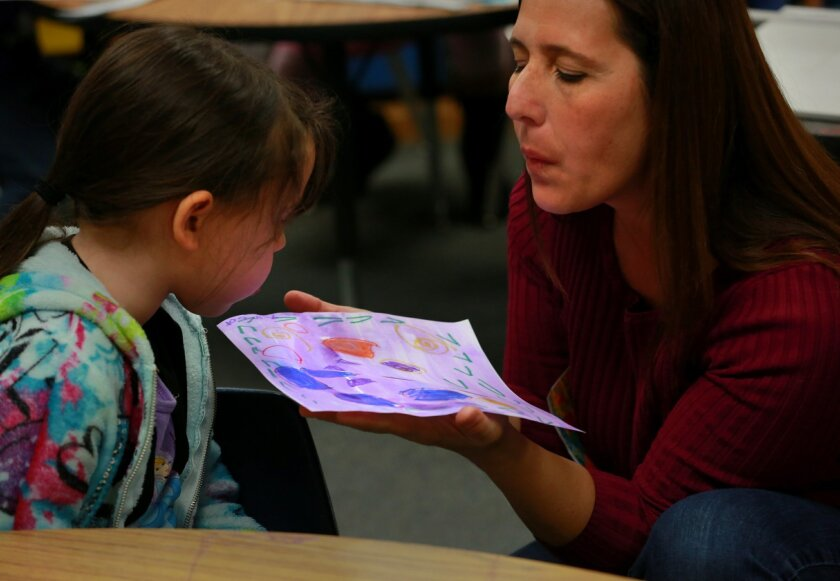 Kindergartner Amber Sanford (left) enlists the help of Cathy Hamilton, coordinator for the Escondido Alliance for Arts Education, in blowing on her watercolor to speed the drying process in class Friday at Juniper Elementary.