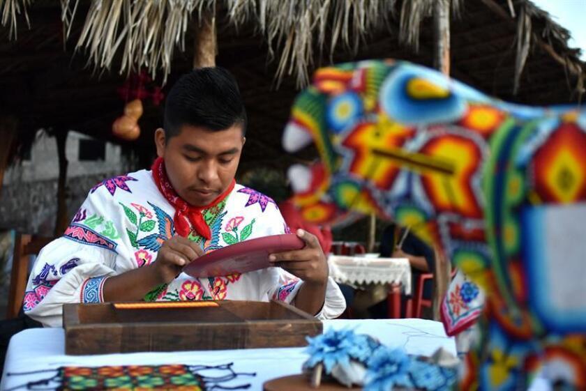 Fotografía del 15 de febrero de 2018, que muestra a un indígena huichol, trabajando en la colonia Zitacua en el municipio de Tepic, Nayarit (México). Los huaraches de cuero, calzones largos de manta, sombreros de palma adornados con plumas y chaquiras, y camisas con coloridos bordados típicos de grupos indígenas se mezclan en la cotidianeidad de una mancha urbana sumida en el tránsito vehicular y en las prisas del día a día. EFE