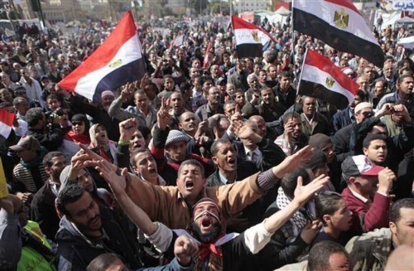 Egyptian protesters wave national flags and chant anti-Supreme Council of Armed Forces (SCAF) slogans during a protest after Friday prayers in Tahrir Square, the focal point of Egyptian uprising, in Cairo, Egypt, Friday, Feb. 10, 2012. (AP Photo/Amr Nabil)