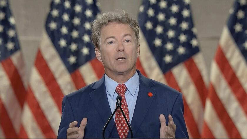 Sen. Rand Paul speaks with U.S. flags behind him.
