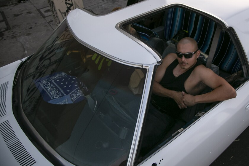 Joey Gallardo of Boyle Heights relaxes in his car during a gathering of Los Angeles lowrider groups.