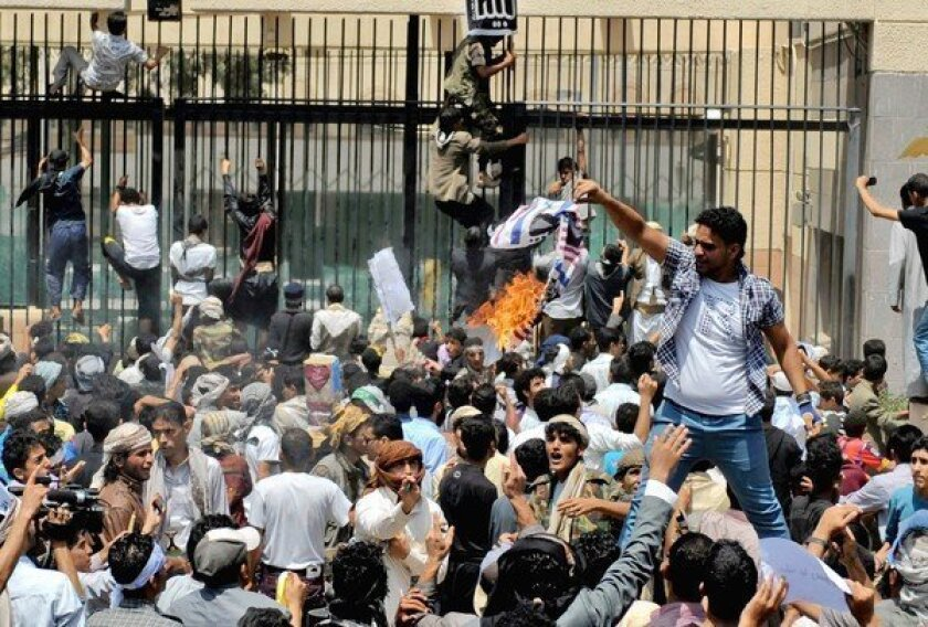 A Yemeni burns a mock U.S. flag as hundreds attack the American Embassy in Sana in protest of a film produced in the U.S. that disparaged the Muslim prophet Muhammad.