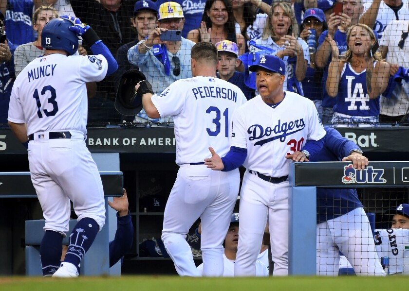 Dodges manager Dave Roberts congratulates Max Muncy after hitting a two-run home run in Game 5 of the NLDS against Washington on Oct. 9, 2019.