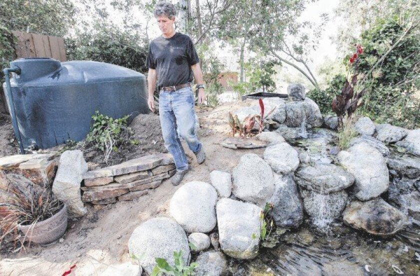 Toone says the exposed large rainwater collection tank just steps from his front door draws attention to his conservation efforts and provokes questions from passers-by.