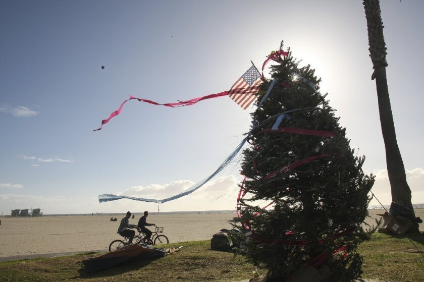 Bikers pass by a Christmas tree at Venice Beach on Dec. 19.
