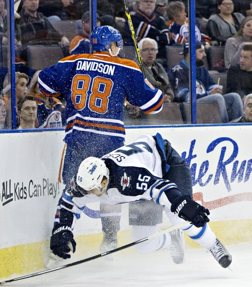Winnipeg Jets' Mark Scheifele (55) is checked by Edmonton Oilers' Brandon Davidson (88) during the first period of an NHL hockey game Saturday, Feb. 13, 2016, in Edmonton, Alberta. (Jason Franson/The Canadian Press via AP)