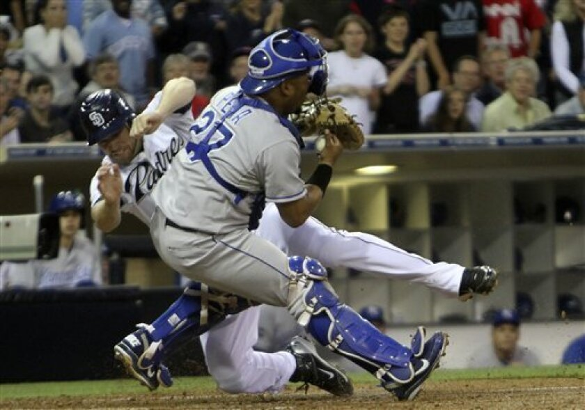 Kansas City Royals catcher Brayan Pena is slammed into by San Diego Padres' Chase Headley in the third inning of a baseball game Monday, June 27, 2011 in San Diego. Headley was out trying to score from first on a double by Ryan Ludwick.  (AP Photo/Lenny Ignelzi)