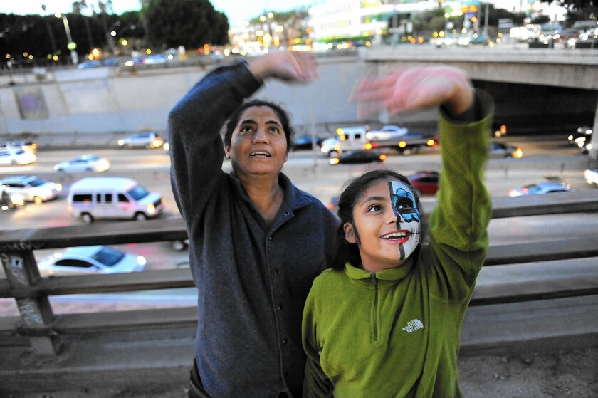 Lucia Sanchez, left, and her 9-year-old daughter Laura wave to inmates inside the Los Angeles Metropolitan Detention Center during the National Day Laborer Organizing Network's 4th Chant Down the Walls concert.
