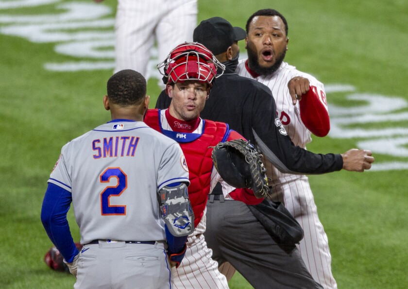 Philadelphia Phillies relief pitcher Jose Alvarado, right, has an altercation with New York Mets' Dominic Smith (2) as catcher Andrew Knapp tries to intervene after Smith struck out swinging in the eighth inning of a baseball game, Friday, April 30, 2021, in Philadelphia. (AP Photo/Laurence Kesterson)