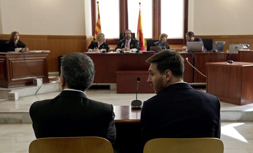 Barcelona's Lionel Messi, right, and his father Jorge Horacio Messi sit in court in Barcelona, Spain, Thursday June 2, 2016. Lionel Messi denied having knowledge of the tax issues that led to fraud charges against him, saying Thursday he signed documents without reading them because he trusted his