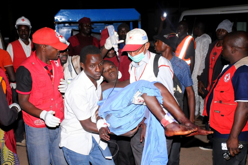 Rescue workers carry an injured victim of twin bombings in the Nigerian city of Jos to a hospital on Dec. 11.
