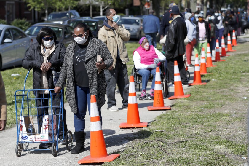 Backers of direct-cash payment programs such as universal basic income say such efforts could help people struggling with basic needs, such as these Chicago residents lined up for a food giveaway sponsored by the Greater Chicago Food Depository during the pandemic.