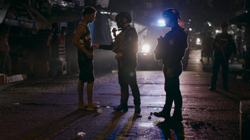 "Late night interrogation of residents suspected of drug dealing in Caloocan, Manila, by police in the documentary ""On the President's Orders."""