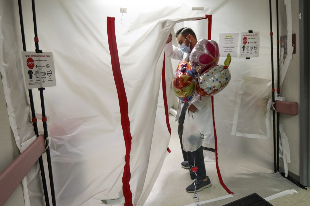 Dr. Imran Siddiqui enters negative pressure enclosure with balloons for his patient.